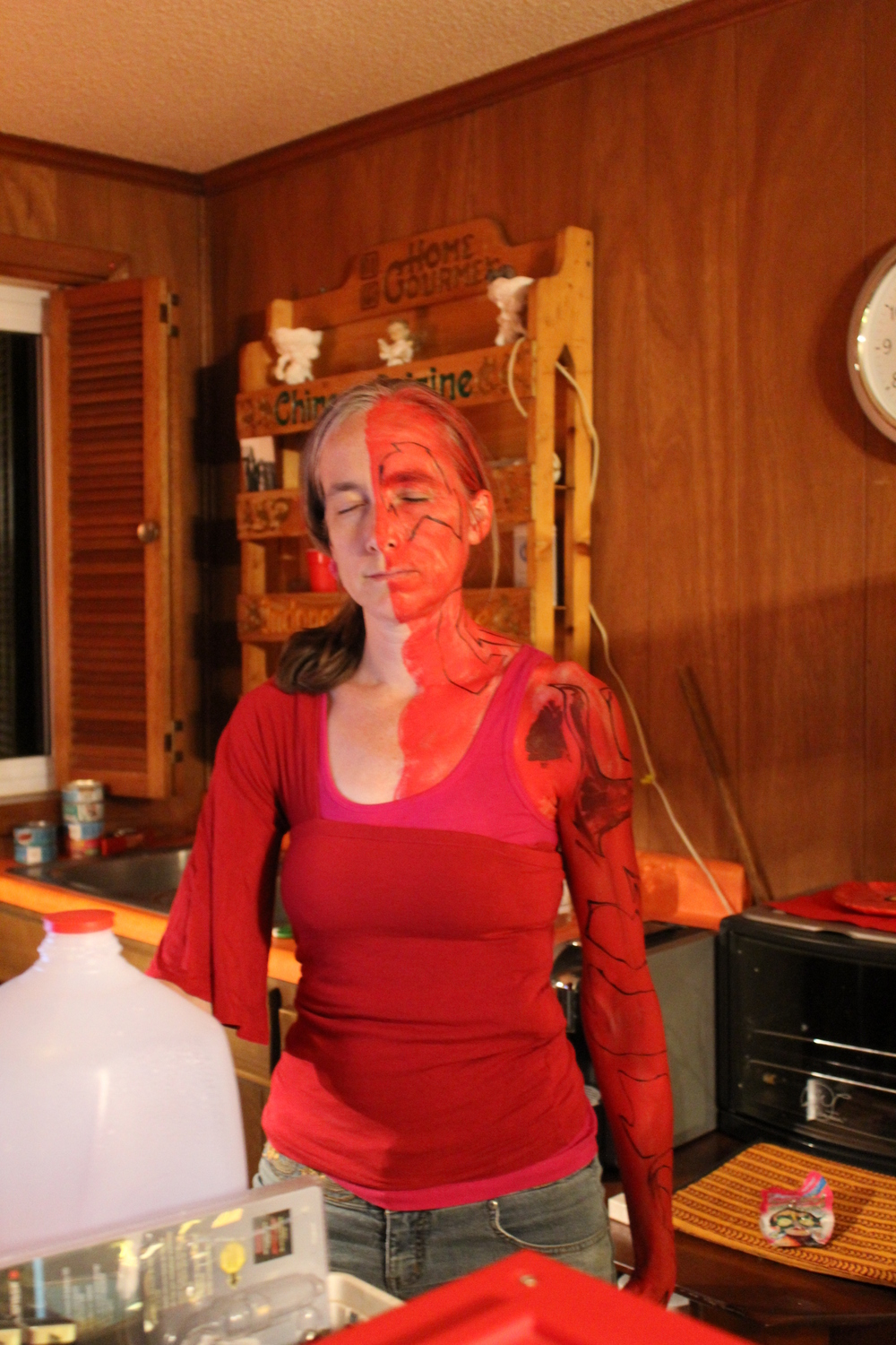 My mom partway through being painted.  The red is lava and the black shapes are going to be crusty lava.  The red was grease paint and acrylic paint and red sharpie marker.