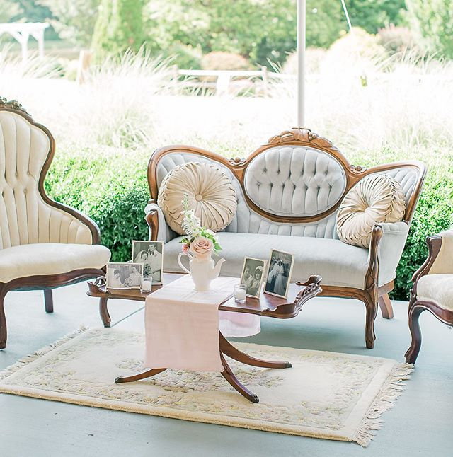 A lounge area is a wonderful idea for relaxing during the wedding. But decor for the table is not typically thought of. This bride added her family pictures to the seating area, which was such a nice touch!  @thecamelliagardens  @clickawayphoto
