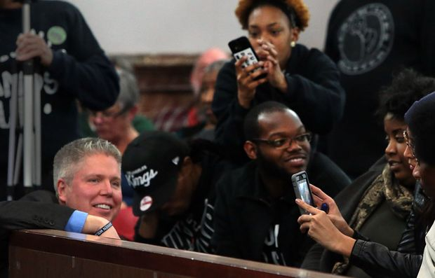 """Protesters photograph Jeff Roorda, business manager of the St. Louis Police Officers Association, as he wears a bracelet that says """"I am Darren Wilson"""" at a meeting of a proposed civilian oversight review board at City Hall on Wednesday, Jan. 28, 2015. Photo by Robert Cohen, rcohen@post-dispatch.com"""