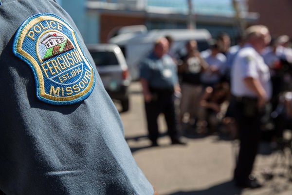 Ferguson, Mo., police officers at a news conference in August. A Justice Department reportwill force Ferguson officials to either negotiate a settlement with the department or face being sued by it on charges of violating the Constitution.  Credit: Whitney Curtis for The New York Times