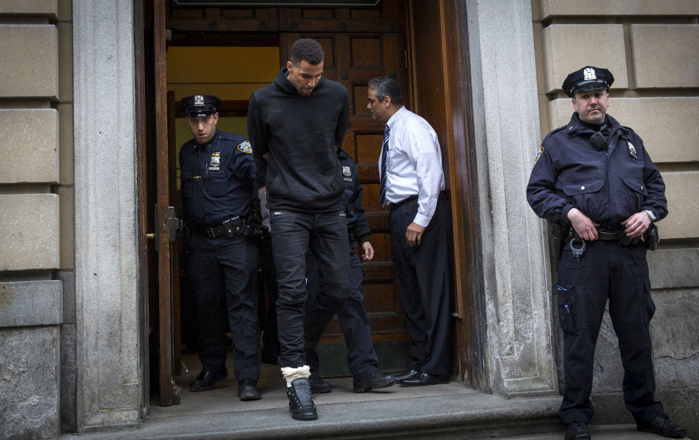NBA player Thabo Sefolosha of the Atlanta Hawks is escorted out of the NYPD's 10th Precinct with a fractured fibula on April 8, 2015. (Reuters/Andrew Kelly)