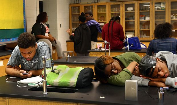 Normandy High honors student Cameron Hensley (left), a senior, checks his phone as some students sleep away physics class on Thursday, April 30, 2015. Though the teacher was inside the classroom the entire class period, no instruction occurred. Instead, the teacher and many students spent the hour on their phones or practicing for the dance team's upcoming parade. Photo by Robert Cohen, rcohen@post-dispatch.com
