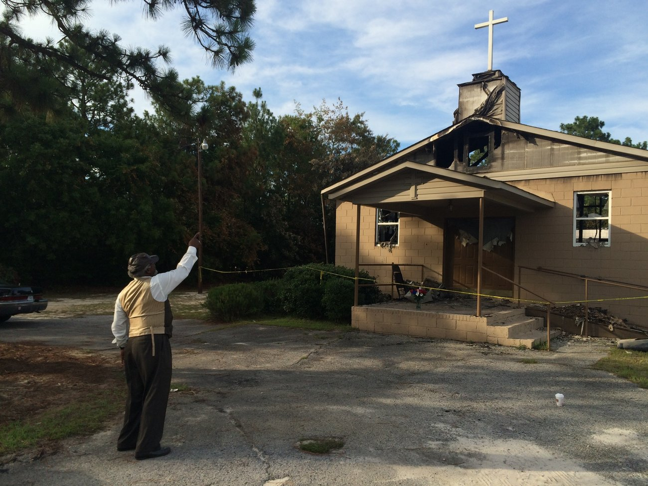 Pastor Bobby Jones points to the cross on top of Glover Grove Baptist Church, where he has preached for more than 30 years. The steeple was one of the only parts of the church left standing.   Will Huntsberry/NPR