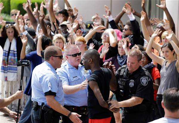 Activist DeRay McKesson is arrested by St. Louis and Federal Protective Service police outside the Thomas F. Eagleton Federal Courthouse on Monday, August 10, 2015. Several protesters were arrested.   Jeff Roberson / AP