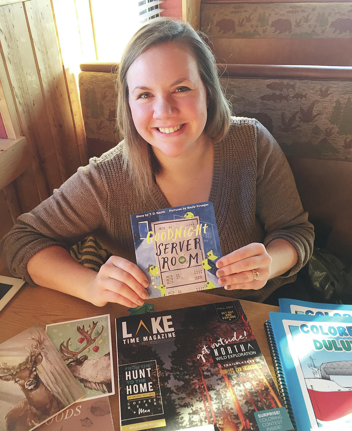 Emily Krueger holds up a childrens book she created the illustrations for. Other projects are spread on the table, including cards, coloring books and an artist book with a short section about her. Jamie Lund/Pine Journal