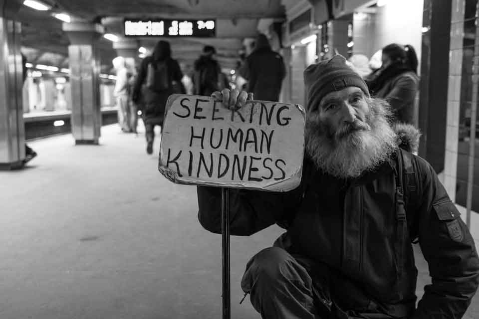"Black and white photo of homeless man in a subway holding a sign that says ""seeking human kindness"""