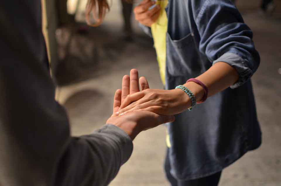 Two people holding hands in such a way that one person appears to be helping the other