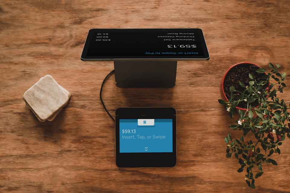 Tablet configured as a point of sale machine on a dark wood table