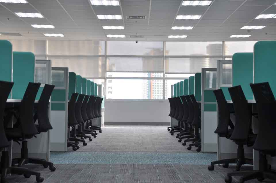 Room filled with teal colored office cubicles and comfortable looking chairs