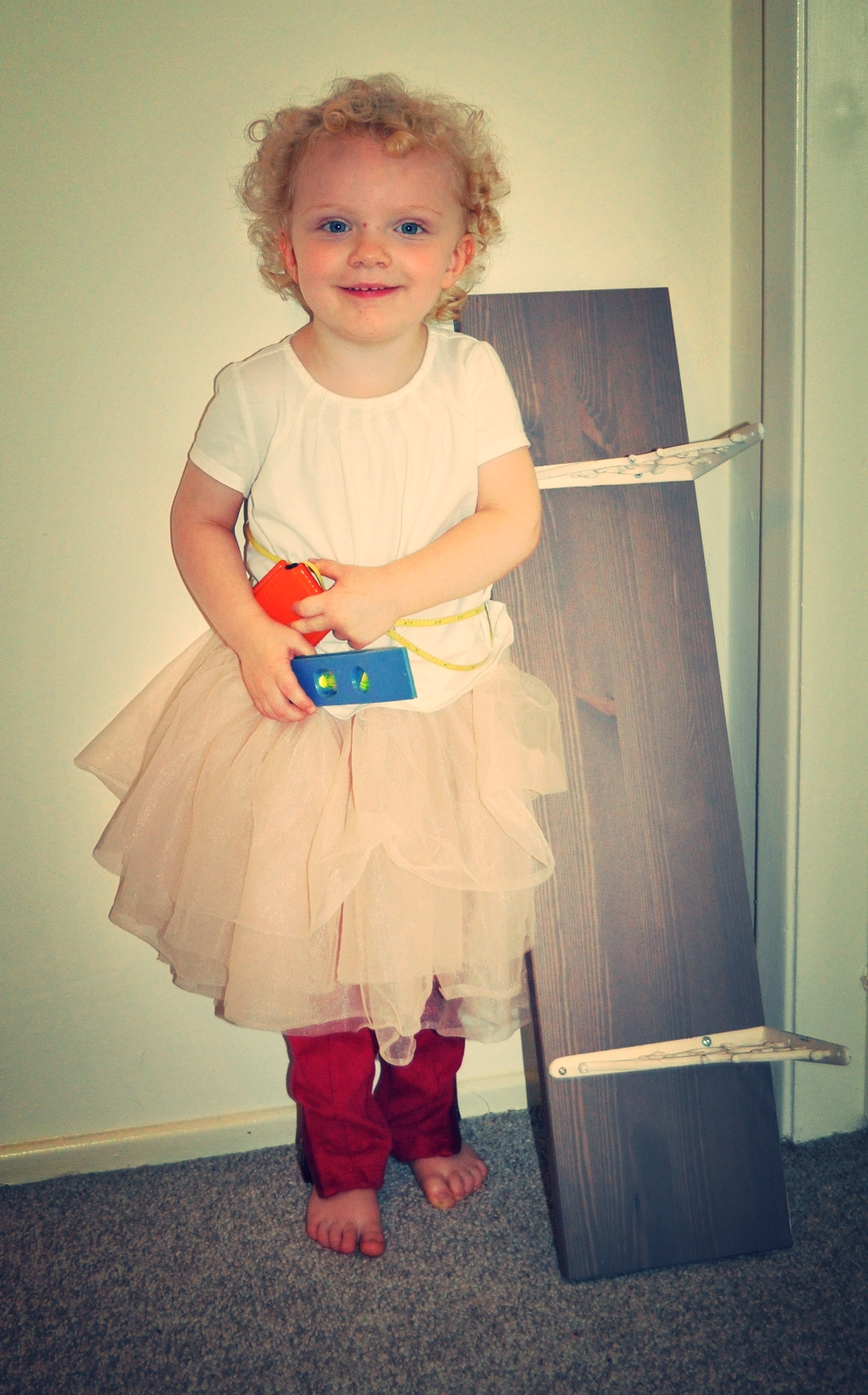 """Toddler G helping with her tape measure """"belt"""" and level."""