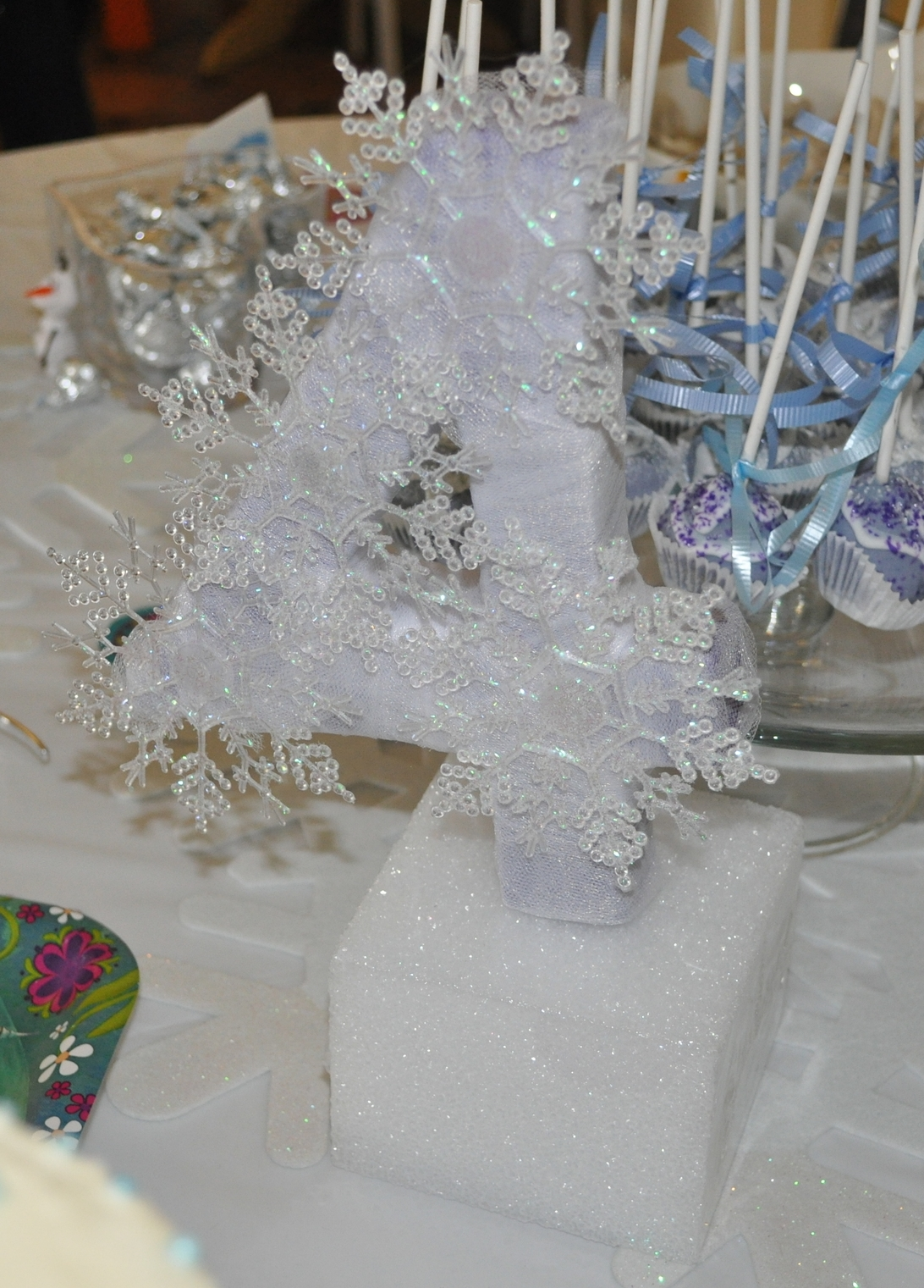A tulle-wrapped paper mache 4 with snowflakes hot-glued on for G