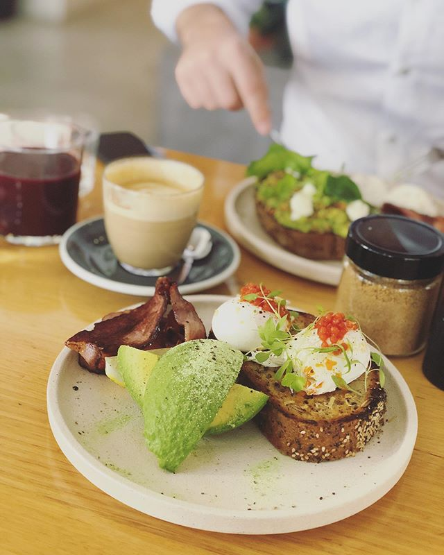 BACK TO BACON   we are back in Australia so it's straight onto bacon, gluten free bread, avocado, soy latte, a latte with fresh milk (no UHT here!), and a beautiful, sunny space. Some may argue that this shot could have been taken anywhere in the world, but I can assure you, THAT IS NOT THE CASE. @nododonuts, you're a sight for hungry, deprived eyes. Conveniently across from our home from home for a few days at @alexperryhotelandapartments 🥳 #weddingseason #brisbanefood #hotellife #traveldiary #lovebrisbane