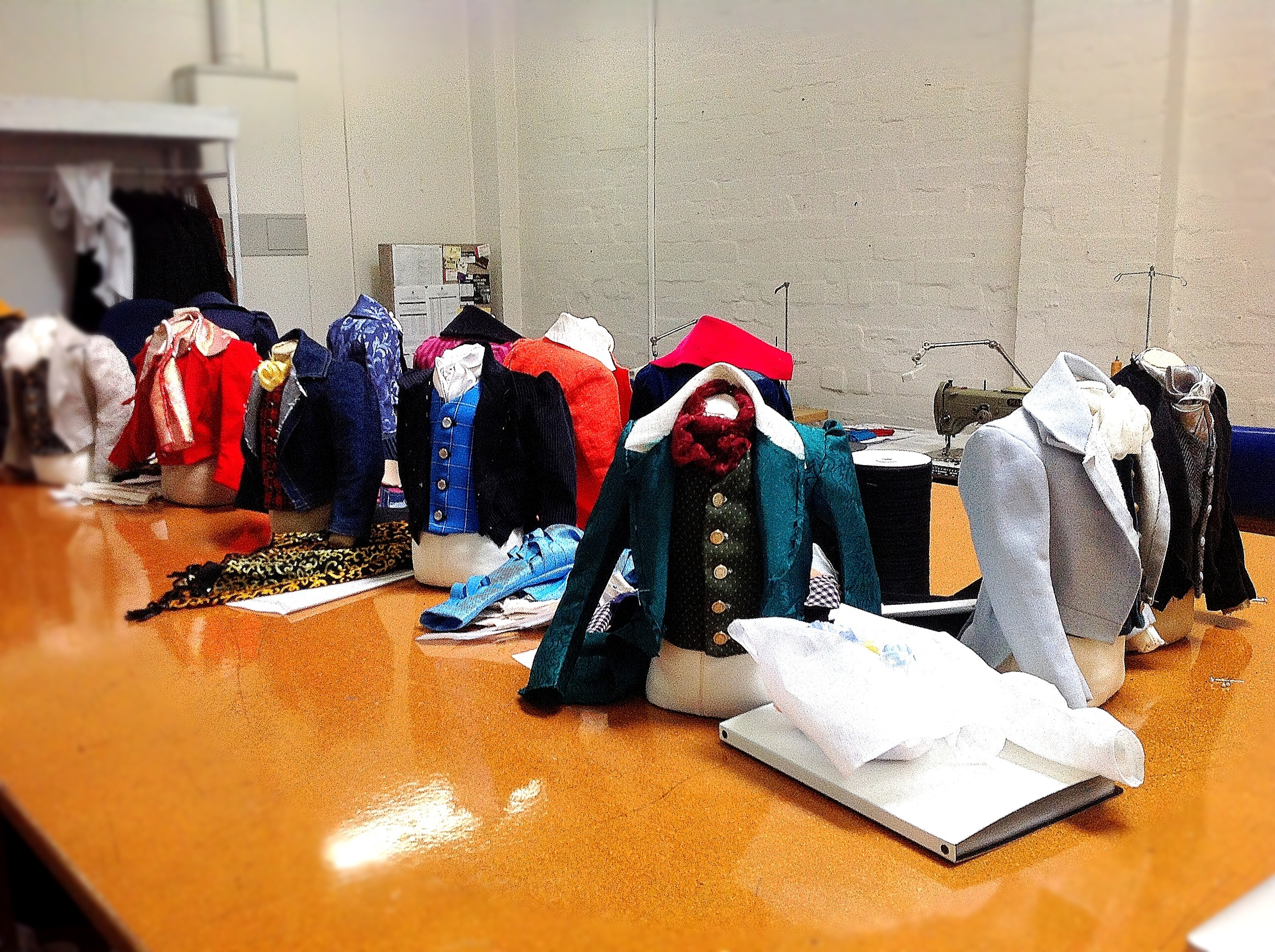 Table full of half scale 19th Century waistcoats and tailcoat toiles