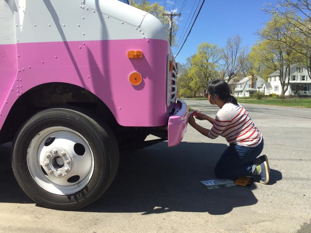 Ice cream in one hand, screwdriver in another--changing the license plates on an Ice Cream Truck for filming