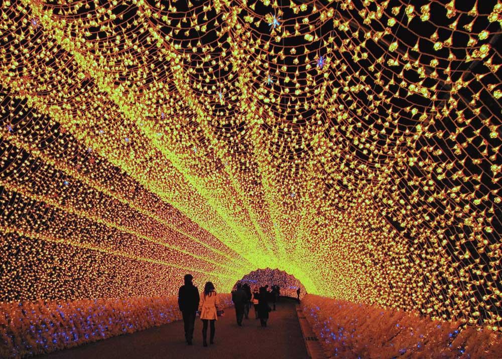 A couple walks through the light tunnel in Nabana no Sato.