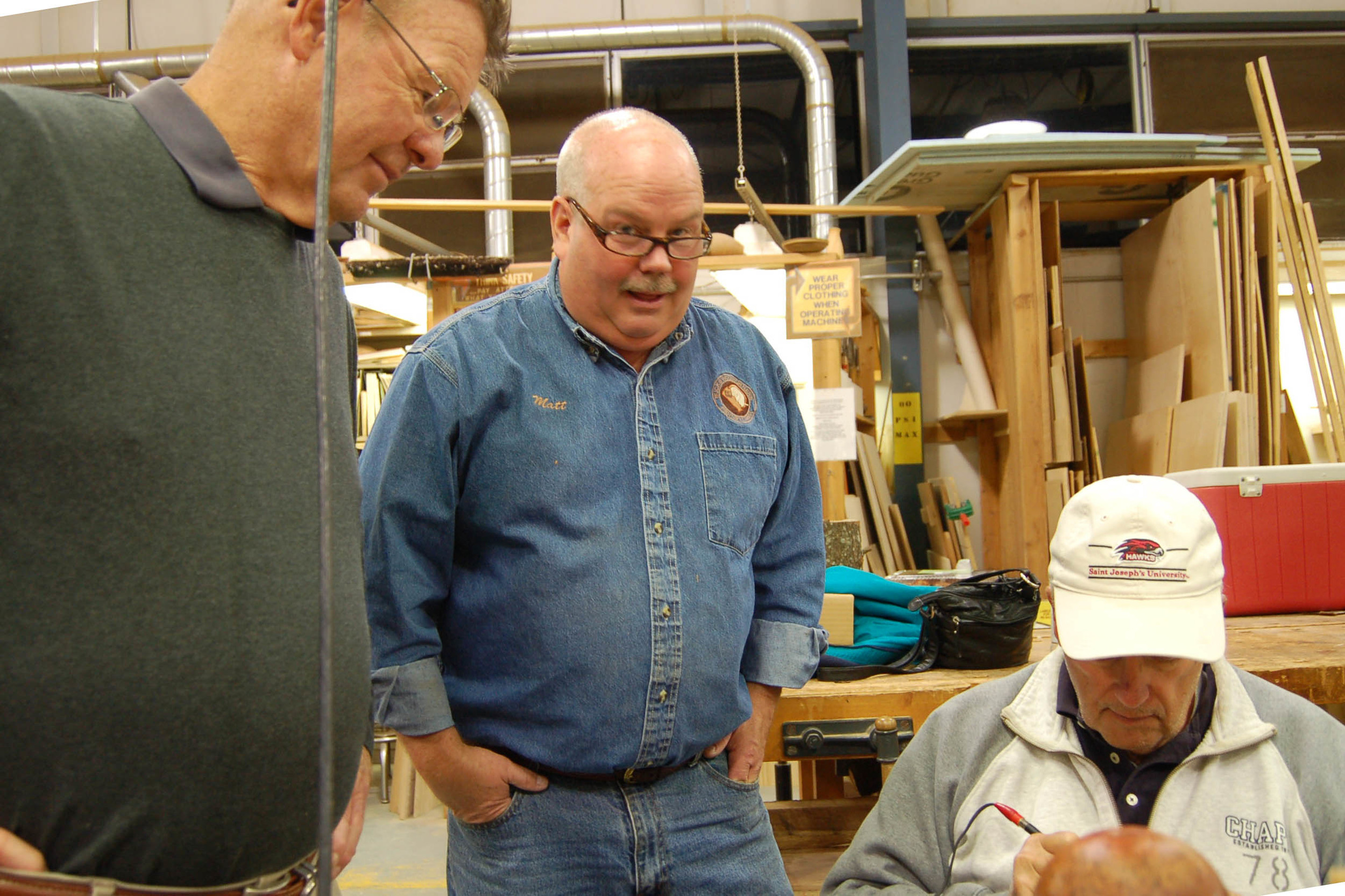 Keith Nelson and Matt Overton look on as John Williams demonstrates his signature pyrography.