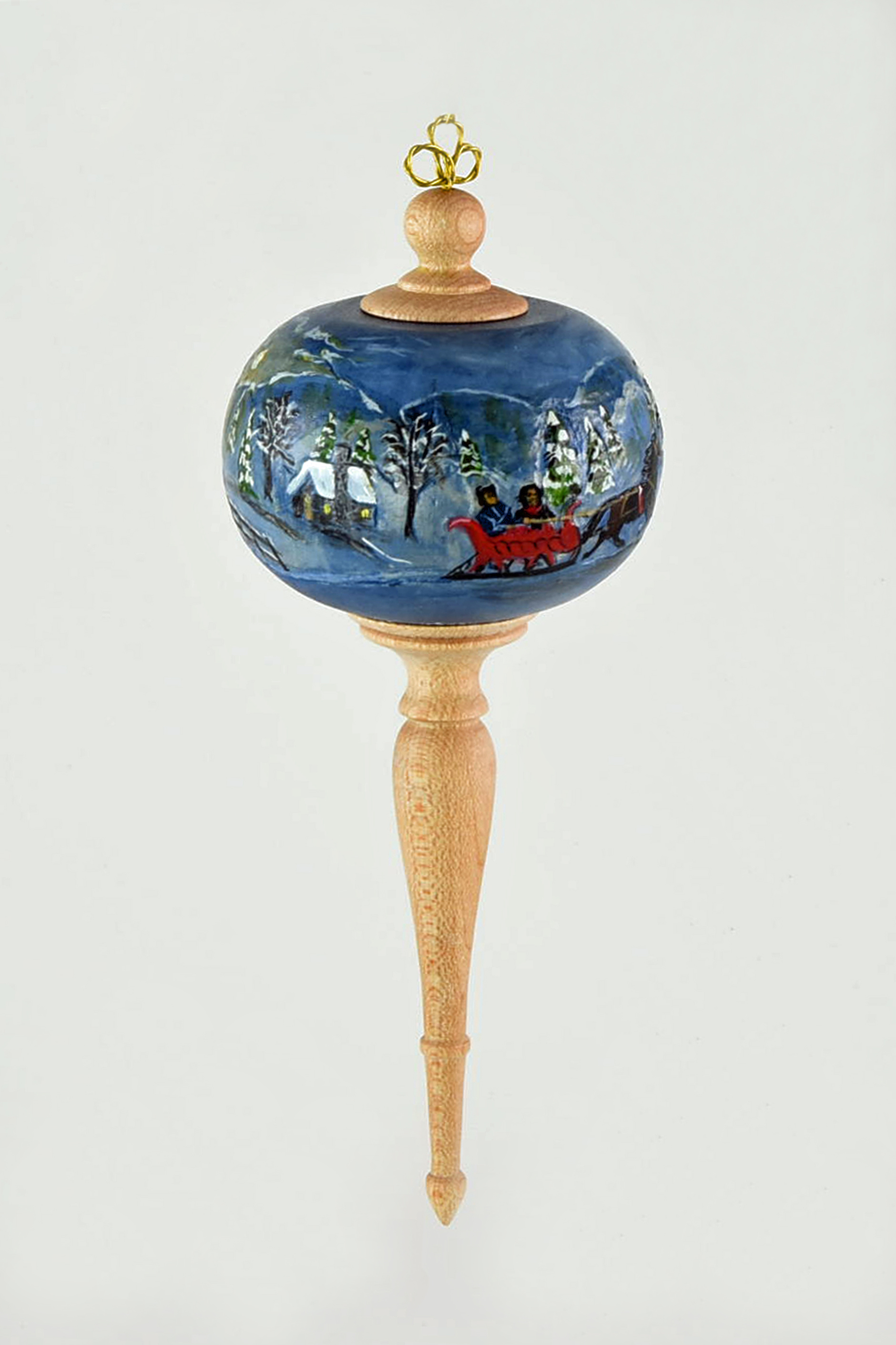 The ball was turned from basswood I wanted to pierce it but had trouble getting an even finish on the inside so I relied on my carving and painting background. I drew a continuous winter scene, relief carved and painted. The finials are made of maple.  -Joyce McCullough