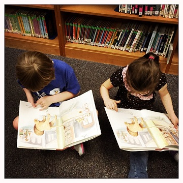 My daughter and her best friend at the school library, reading the same exact page on the same exact book. Taken by her teacher.