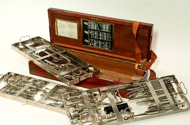 The casket contains three layers of stainless steel instruments and a tourniquet (top right).