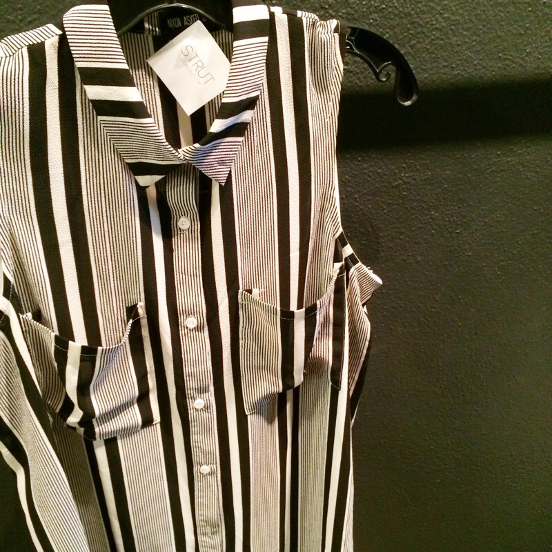 Raquel Greer Gordian displays a picture of a striped button-up sleeveless shirtdress from Strut.
