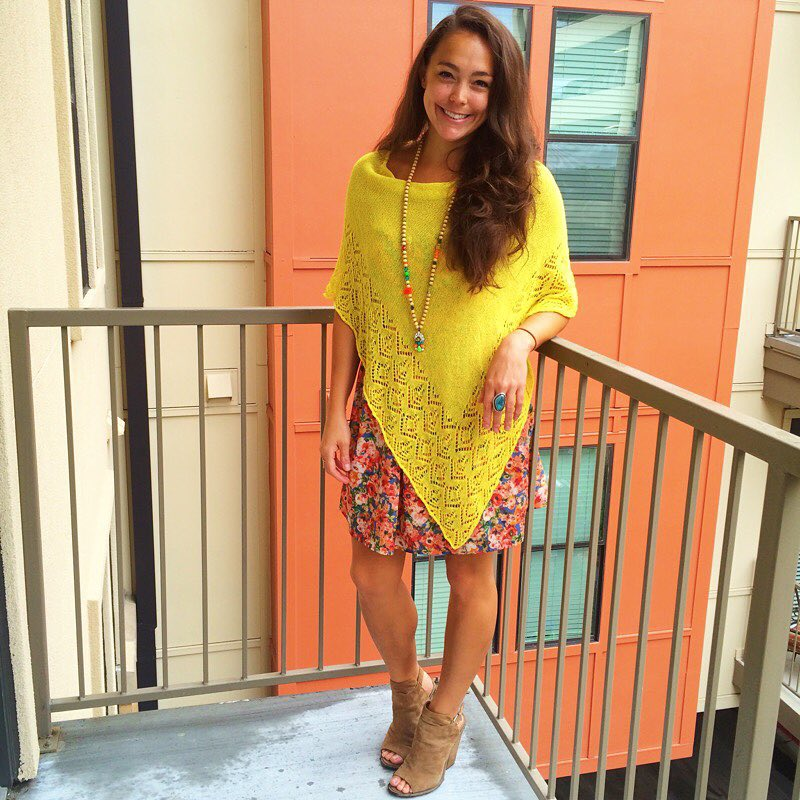 Raquel Greer Gordian models a summer look incorporating a bright yellow poncho, floral dress, beaded tassel necklace, statement ring, and some booties.