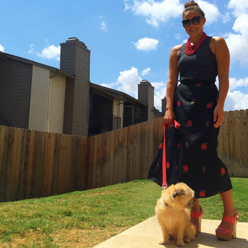 Raquel Greer Gordian models a casual summer look incorporating a black tank, printed maxi skirt, red beaded statement necklace, black cat eye sunglasses, and red platform block heels.