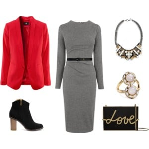 Raquel Greer Gordian displays an outfit that pairs the long sleeve gray dress with a red blazer, black booties, statement jewelry, a black belt, and a black handbag.