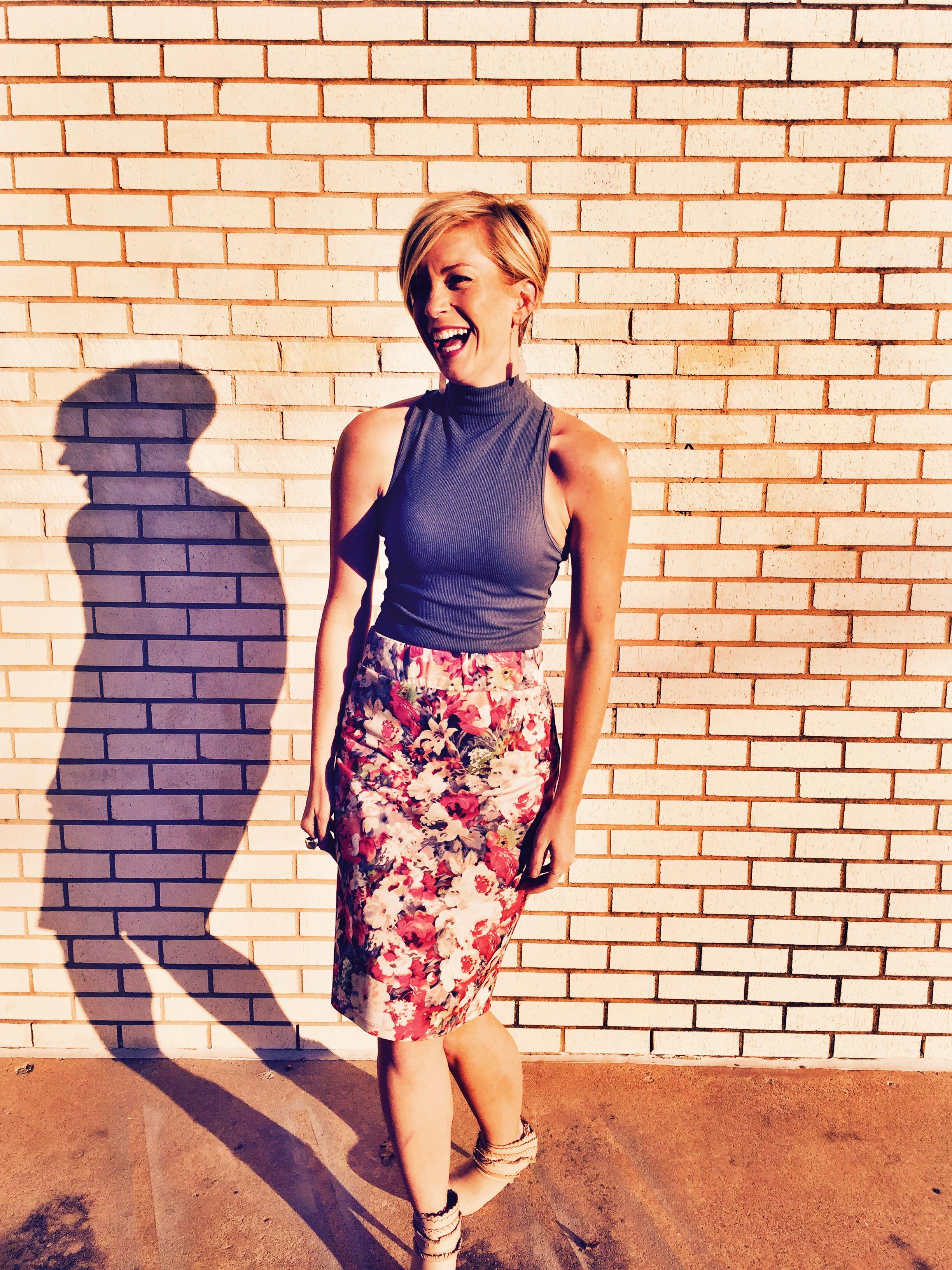 Emily Blanco models a look with a floral pencil skirt, booties, and a gray tank.
