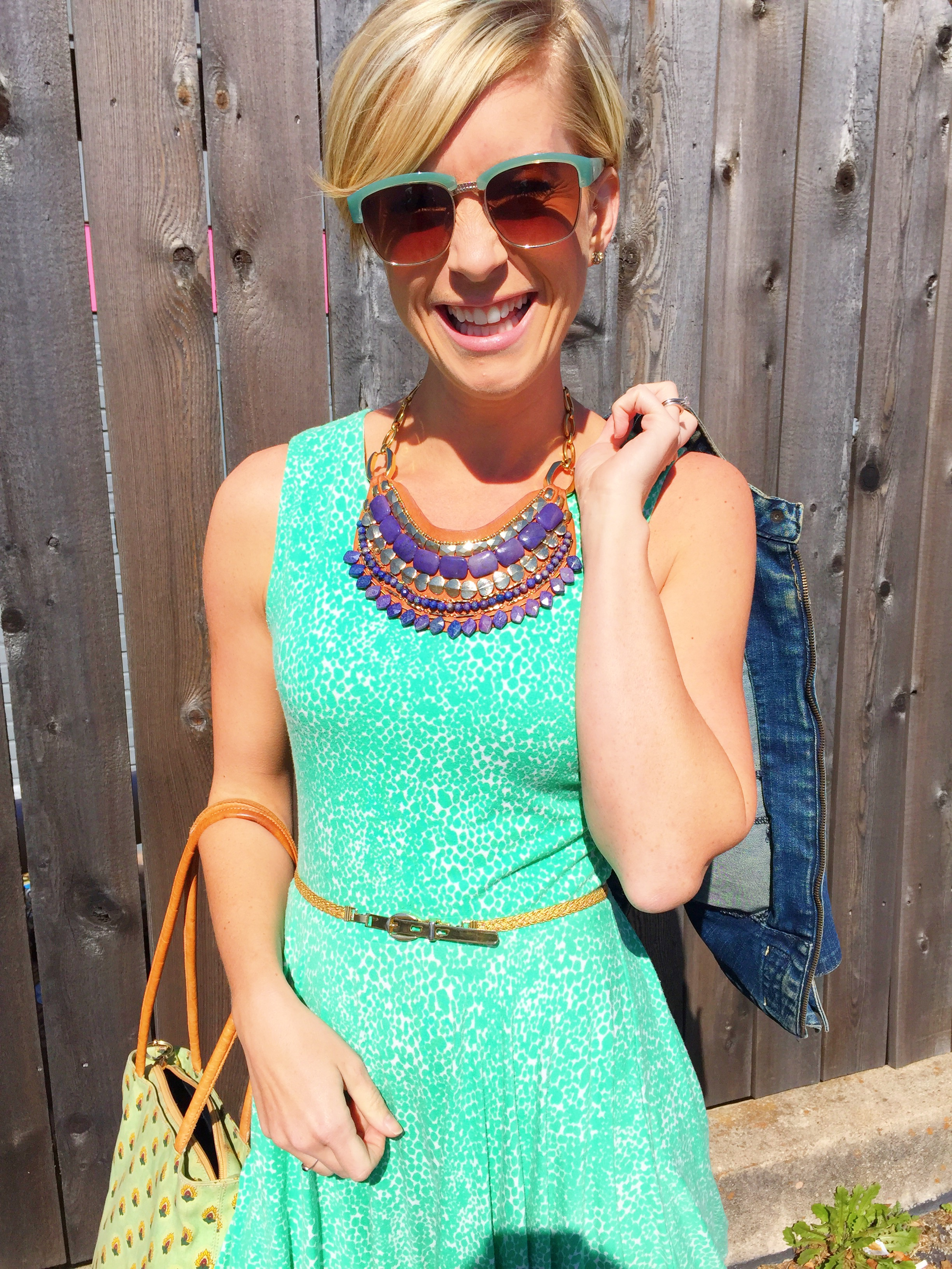 Emily Blanco models a business casual look with a green dress, statement necklace, denim jacket, and a braided belt.