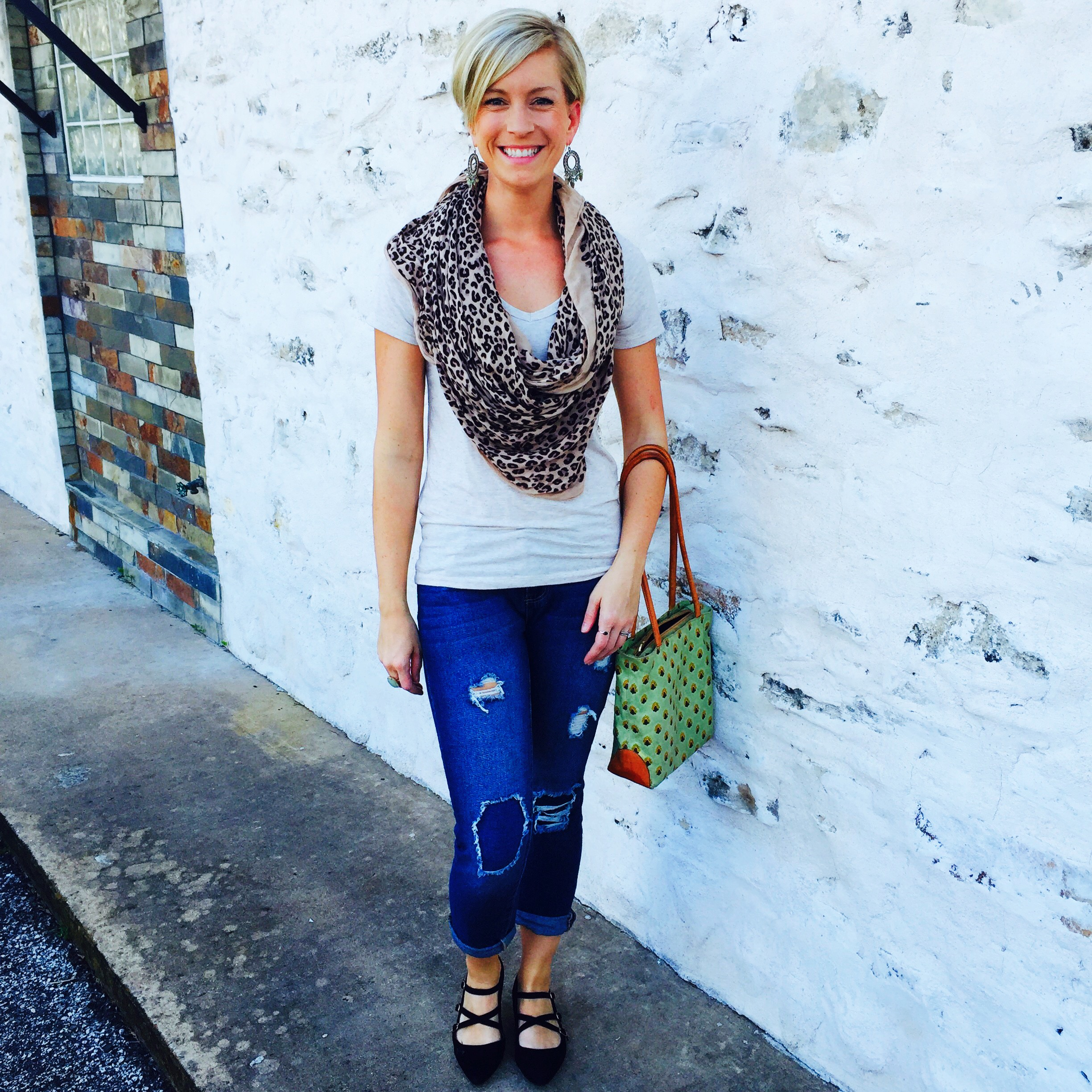 Emily Blanco models a casual look with some ripped jeans, black scrappy flats, a cheetah-print infinity scarf, a simple tee, and some statement earrings.
