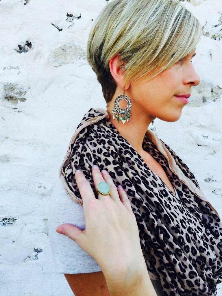 Emily Blanco showcases a pair of statement earrings and a statement ring.