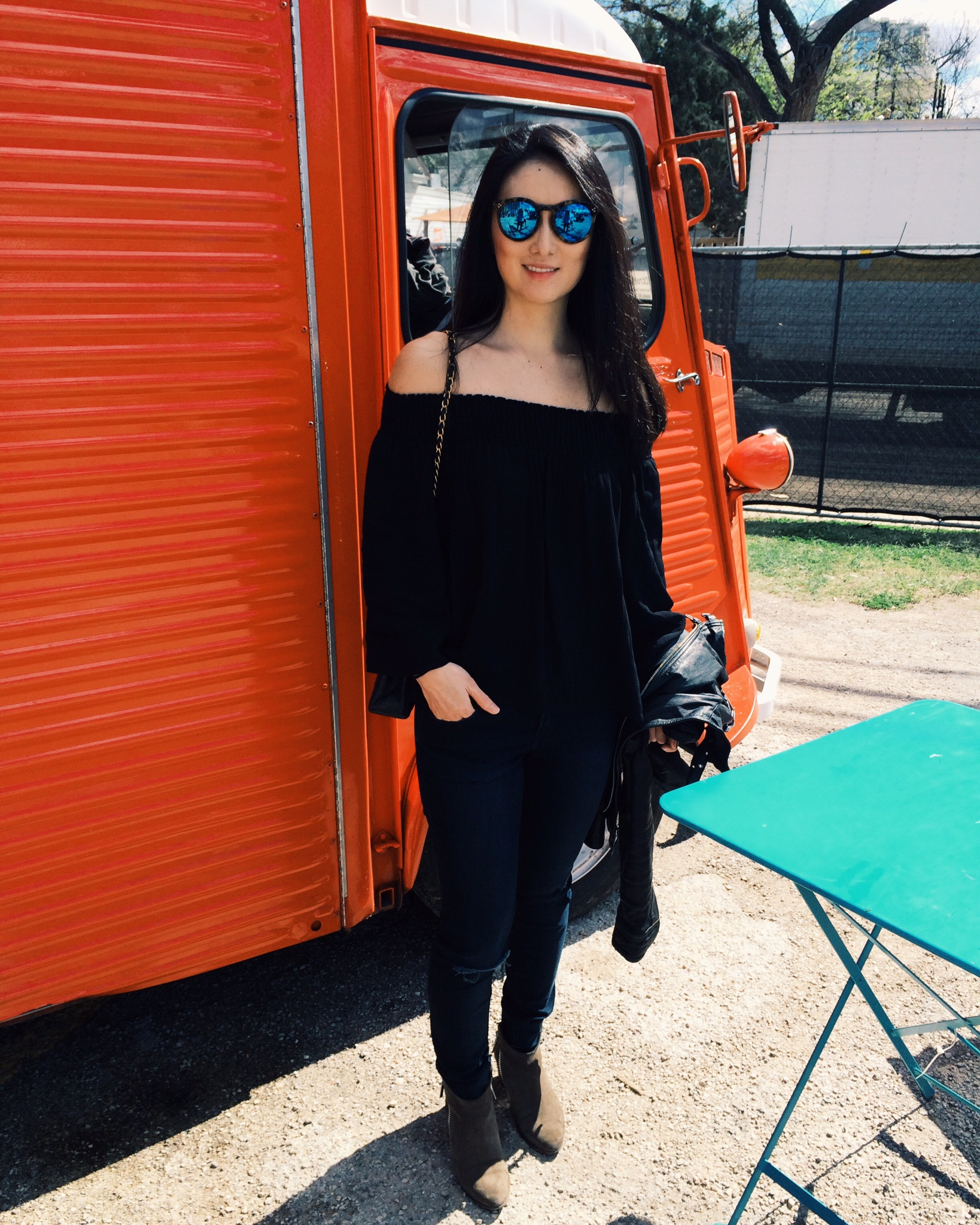 Raquel Greer Gordian shows an image of Grace Yoon's mirrored sunglasses, off-the-shoulder top, jeans, leather moto jacket, and booties for SXSW.