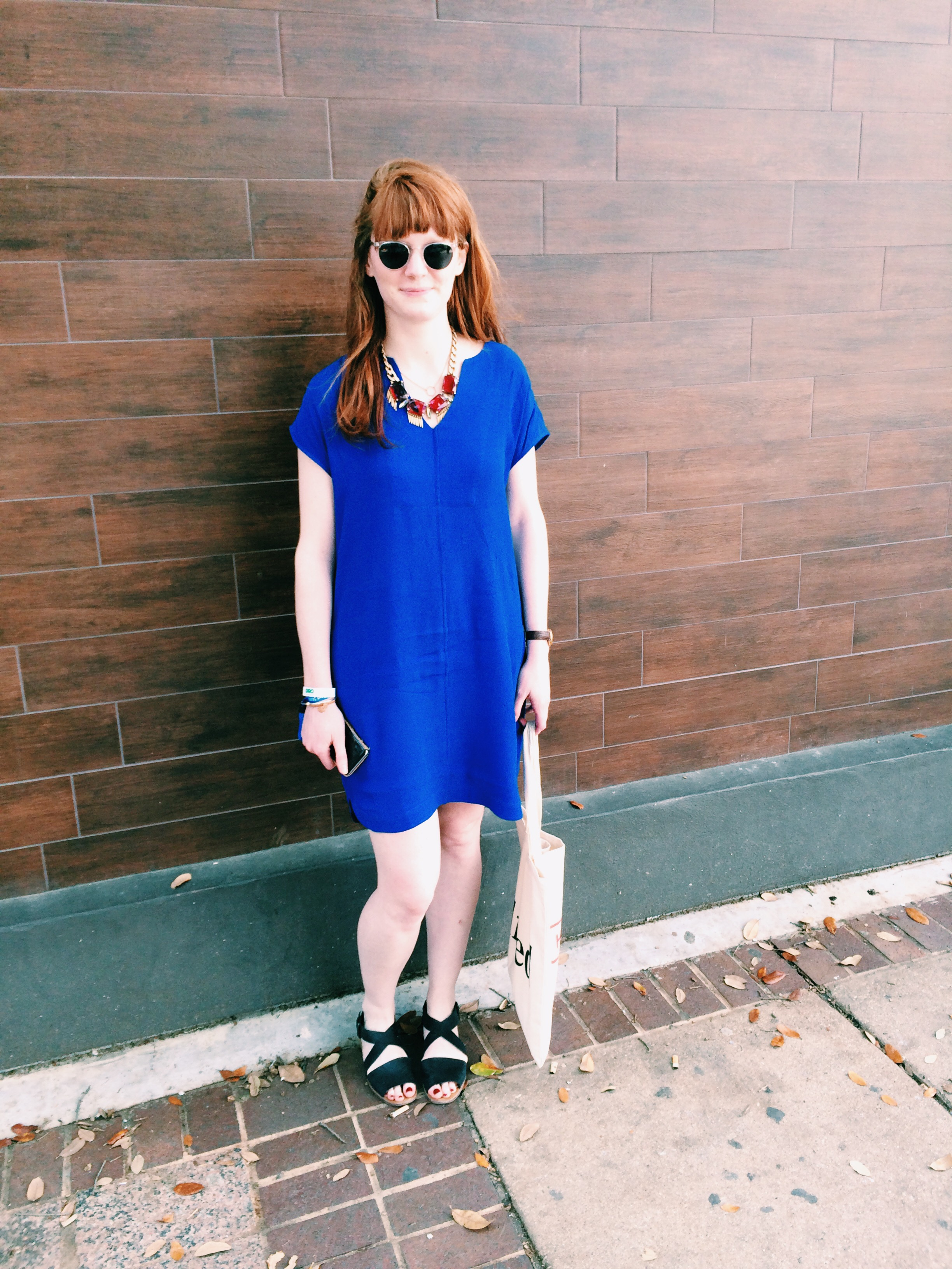 Raquel Greer Gordian shows off Lilla Cosgrove's SXSW outfit, consisting of a blue shift dress, statement necklace, black leather sandals, and round sunnies.