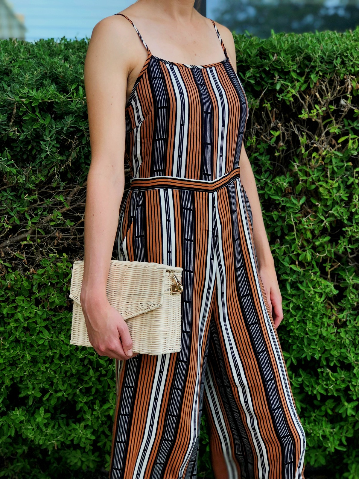 The stripes in the jumpsuit enhance the striped in the bag.