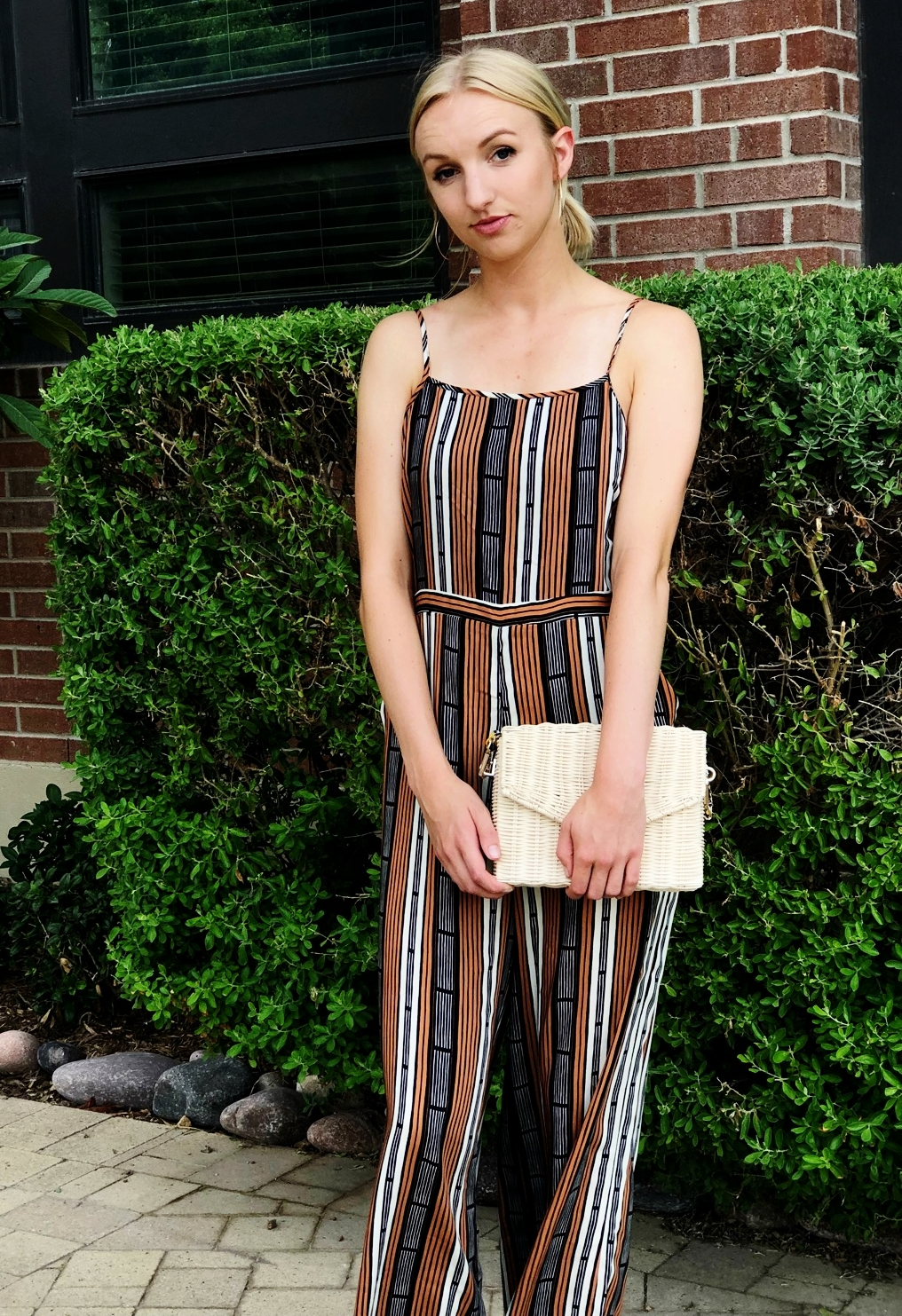 Bailey Bosworth wears a jumpsuit to elongate her silhouette. She finished the look with hoops and the perfect straw bag.
