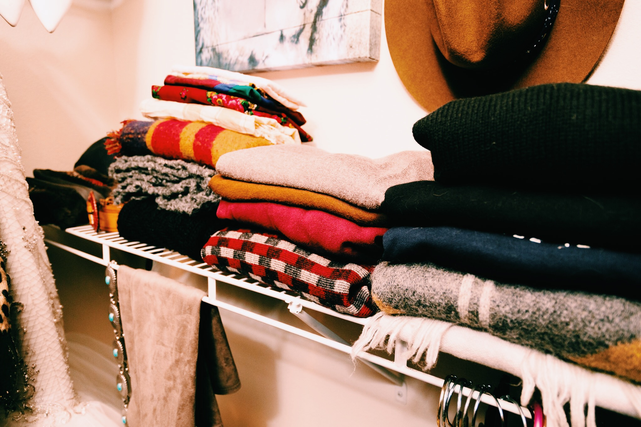 Scarves folded next to sweaters for easy access and styling.