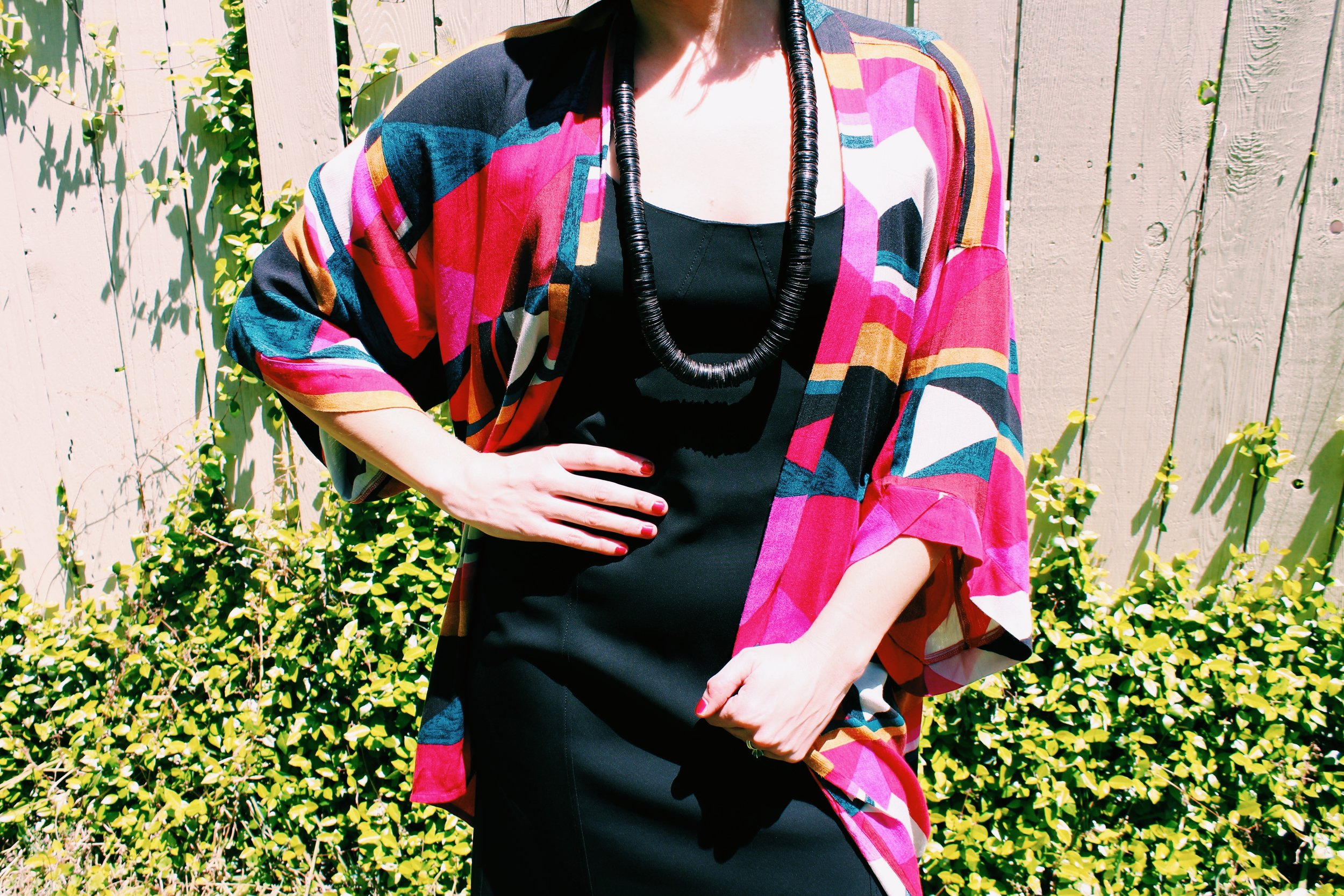 Raquel Greer Gordian adds a vibrant kimono, chevron stacked heels, and a long necklace to a black dress to spruce it up for spring and summer 2019.
