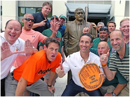 Former University of Miami Hurricanes team members gather round the statue of Ron Fraser (1933-2013),       The Wizard of College Baseball,      at the unveiling ceremony on April 24, 2015.
