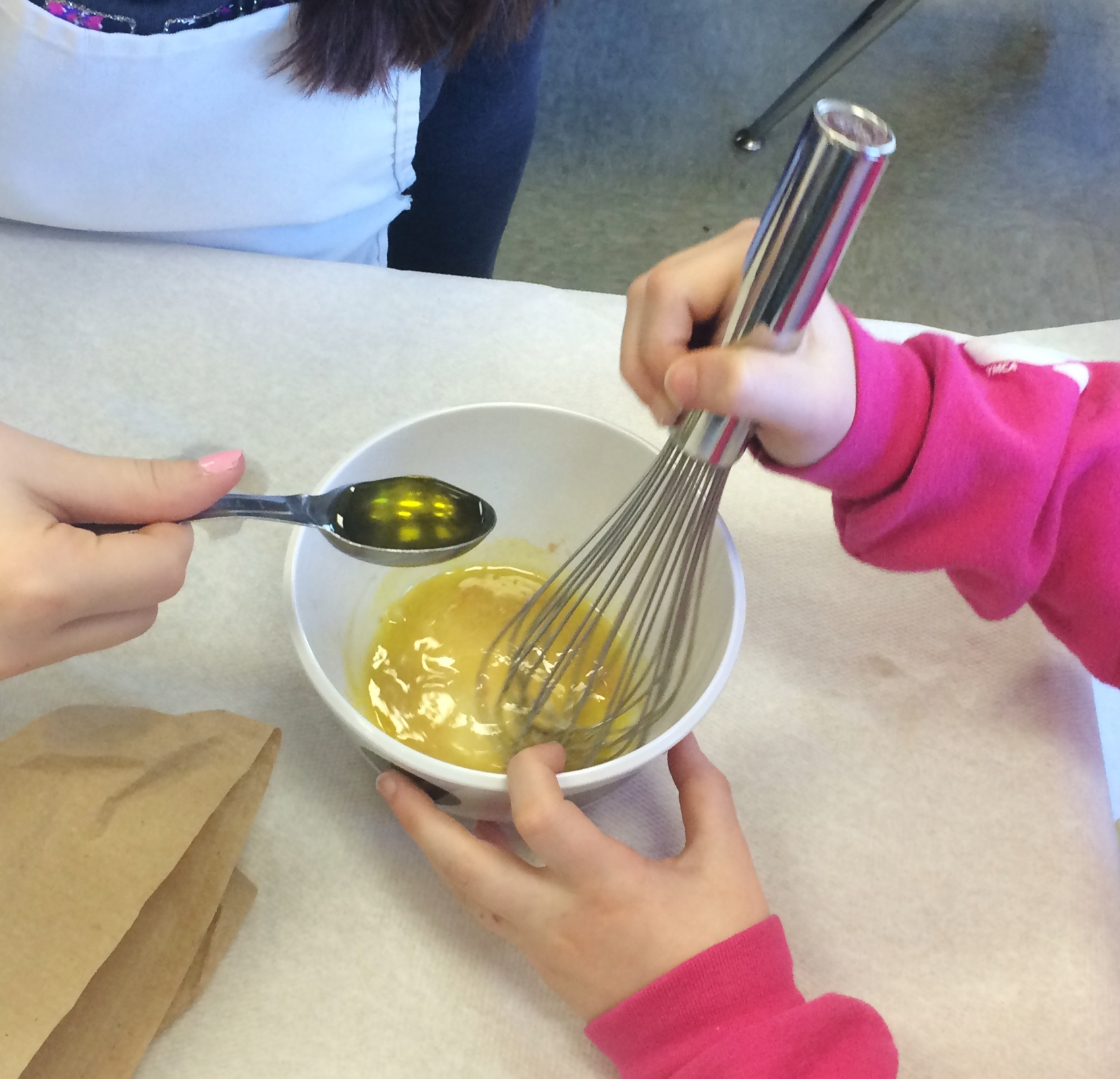 Friends working together to whisk the olive oil into the vinaigrette.