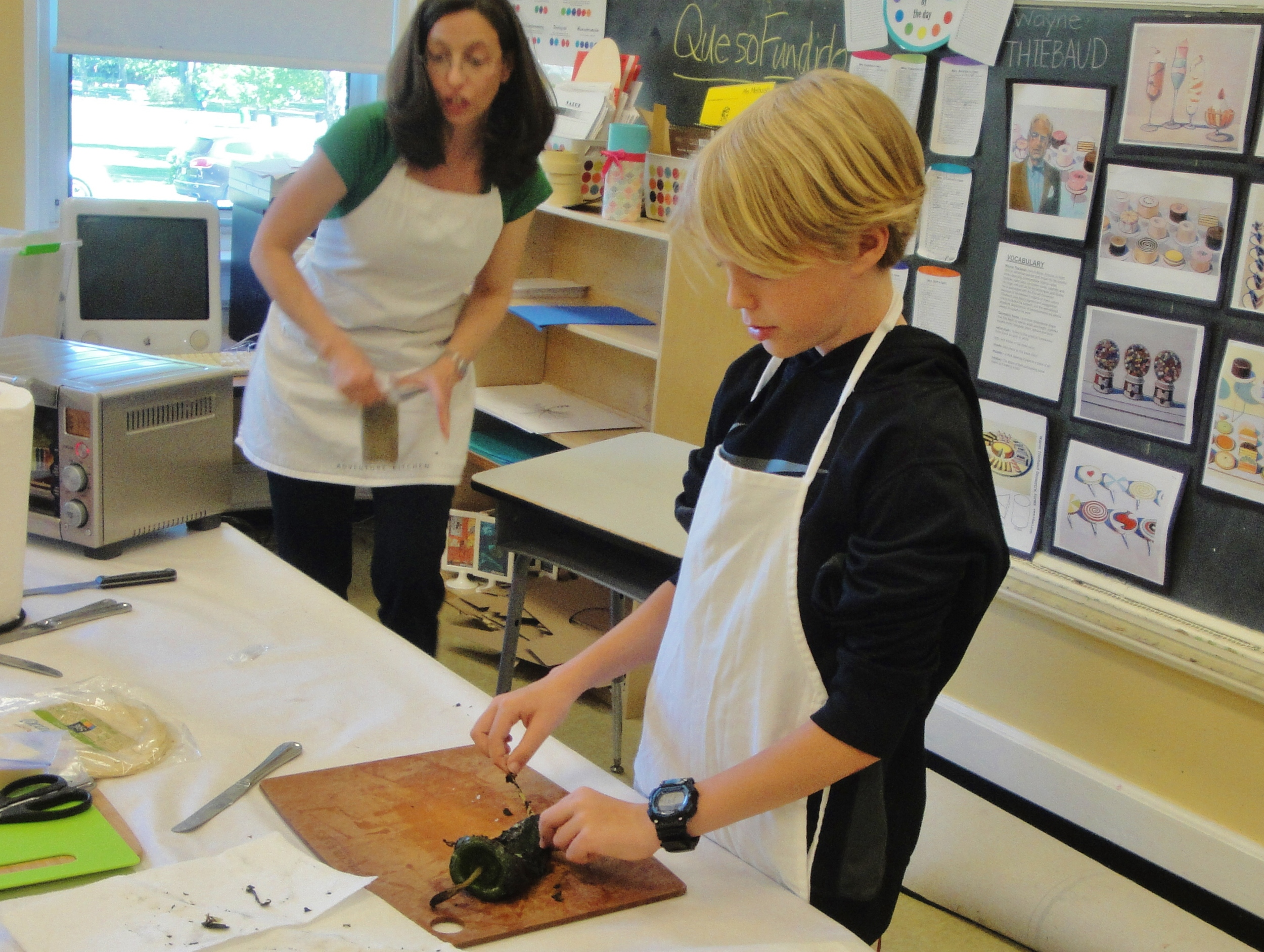 Peeling a roasted Poblano chile (while Ms. Lynley gets the Mexican oregano ready)