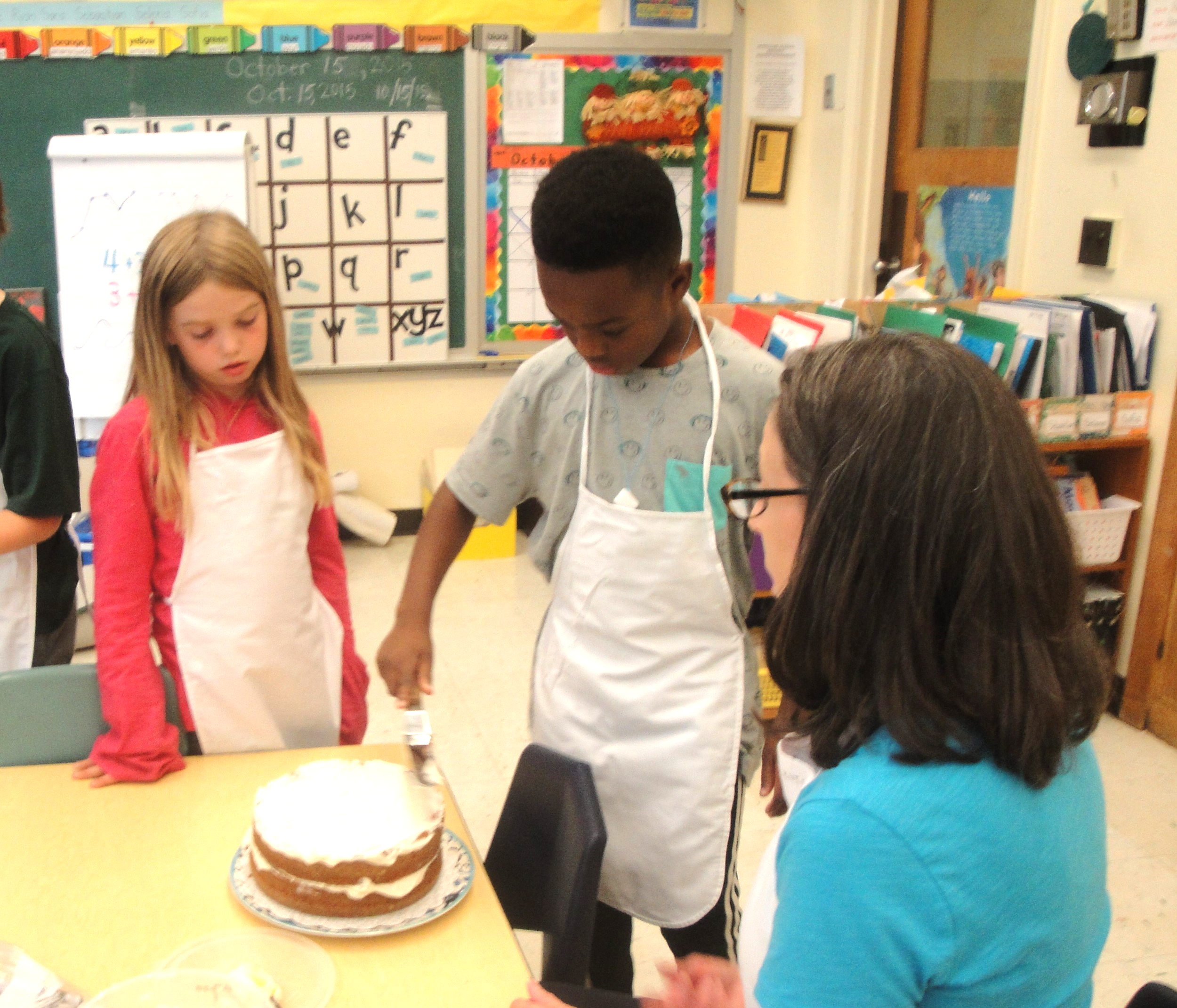 The children take turns frosting the cake.