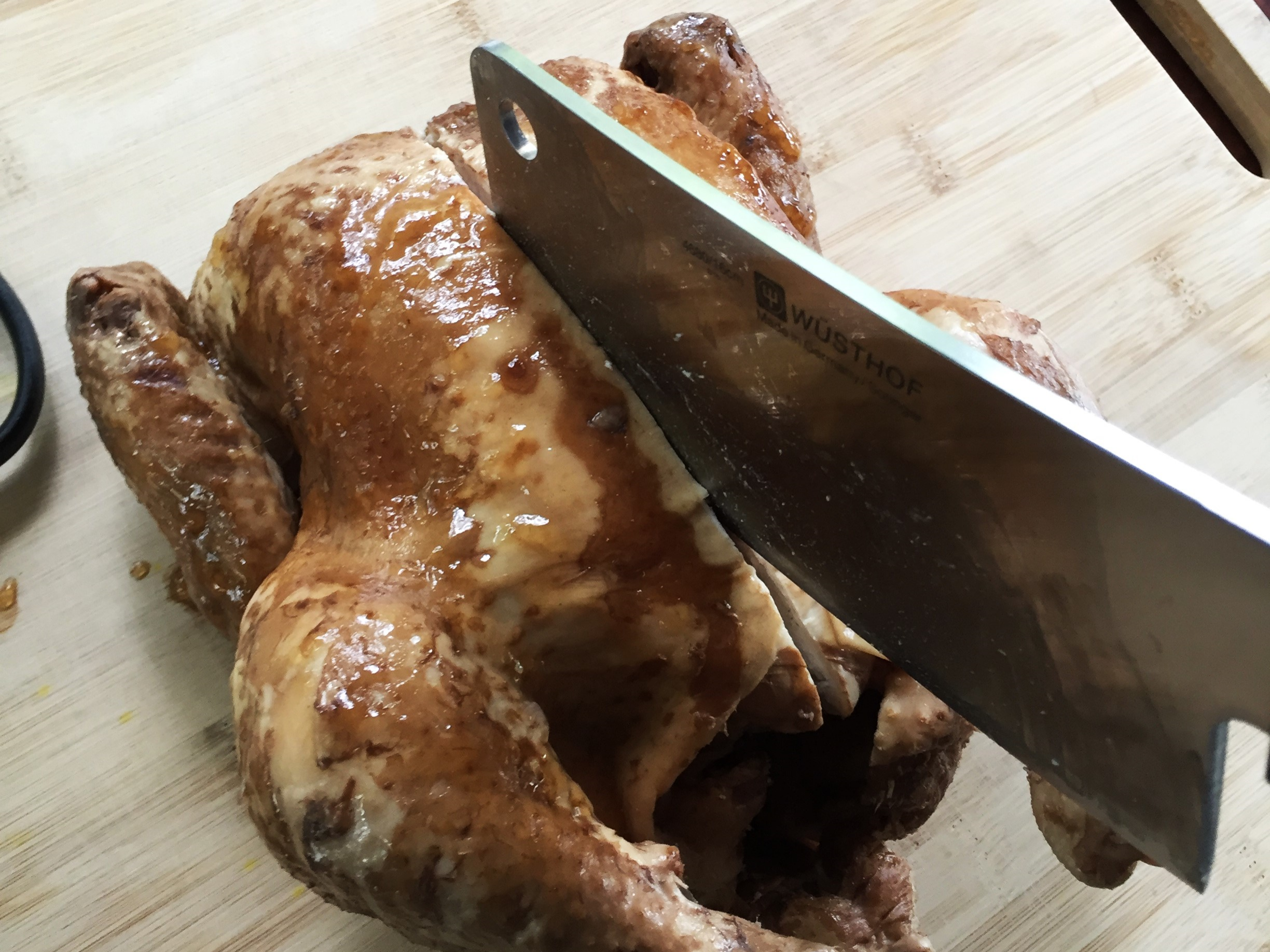 Cutting down through the breastbone and all the way down through the back of the chicken. As you reach the chicken's back, let your knife land to either side of the spine. You'll separate the spine from the other side in a later step.