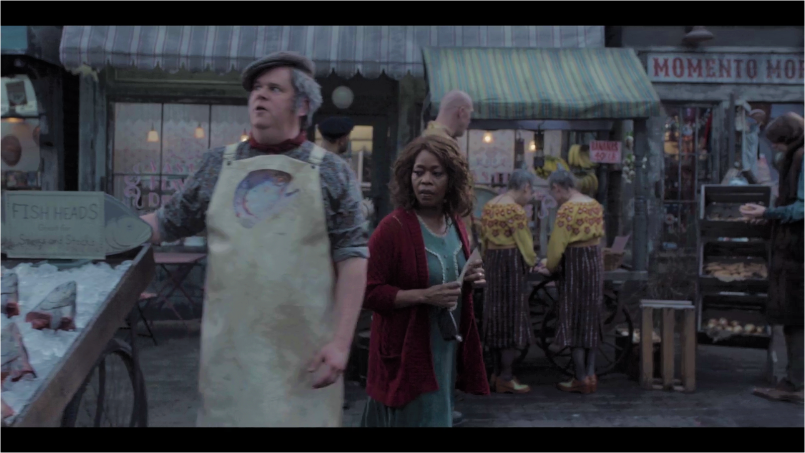 This photograph, obtained at great risk from the Netflix corporation, is one of the few remaining images of the Town Market and Petting Zoo before Hurricane Herman. It must have been taken shortly before the storm, as evidenced by the many strange characters seen milling about, and the nefariously-bookish fish head vendor in the foreground.