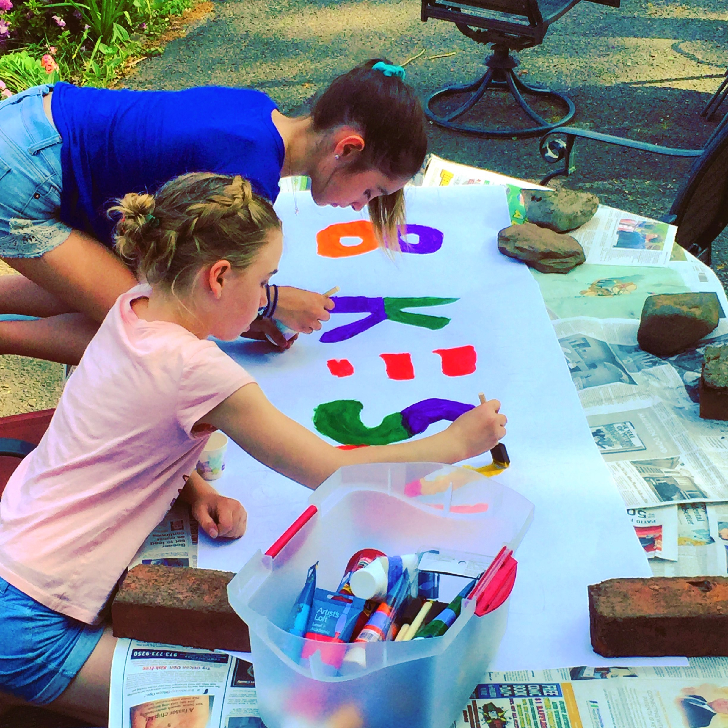 Volunteers Quinn and Elizabeth painting the sign