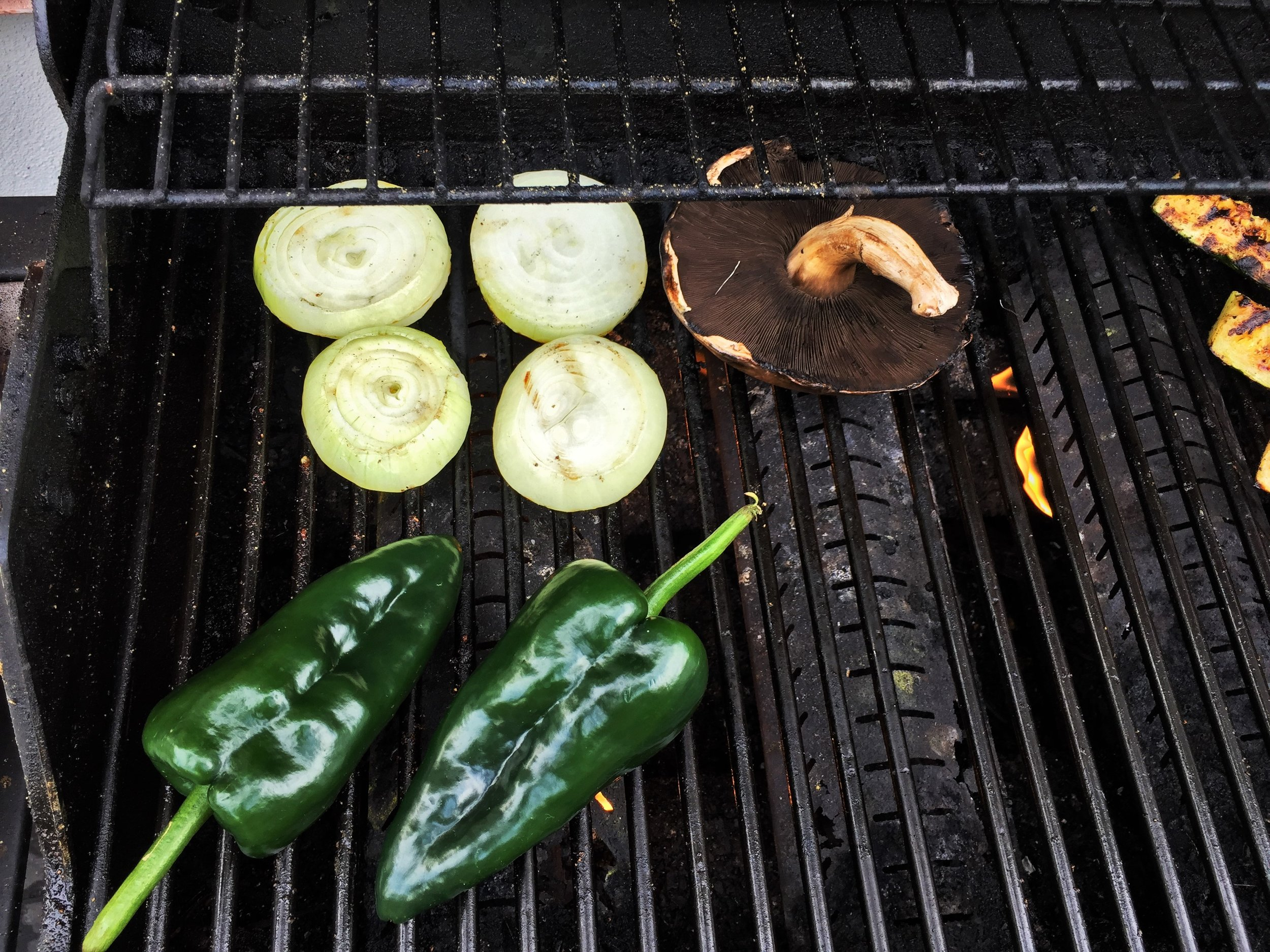 Onion rounds and portobello mushroom sharing the grill with poblano chiles.