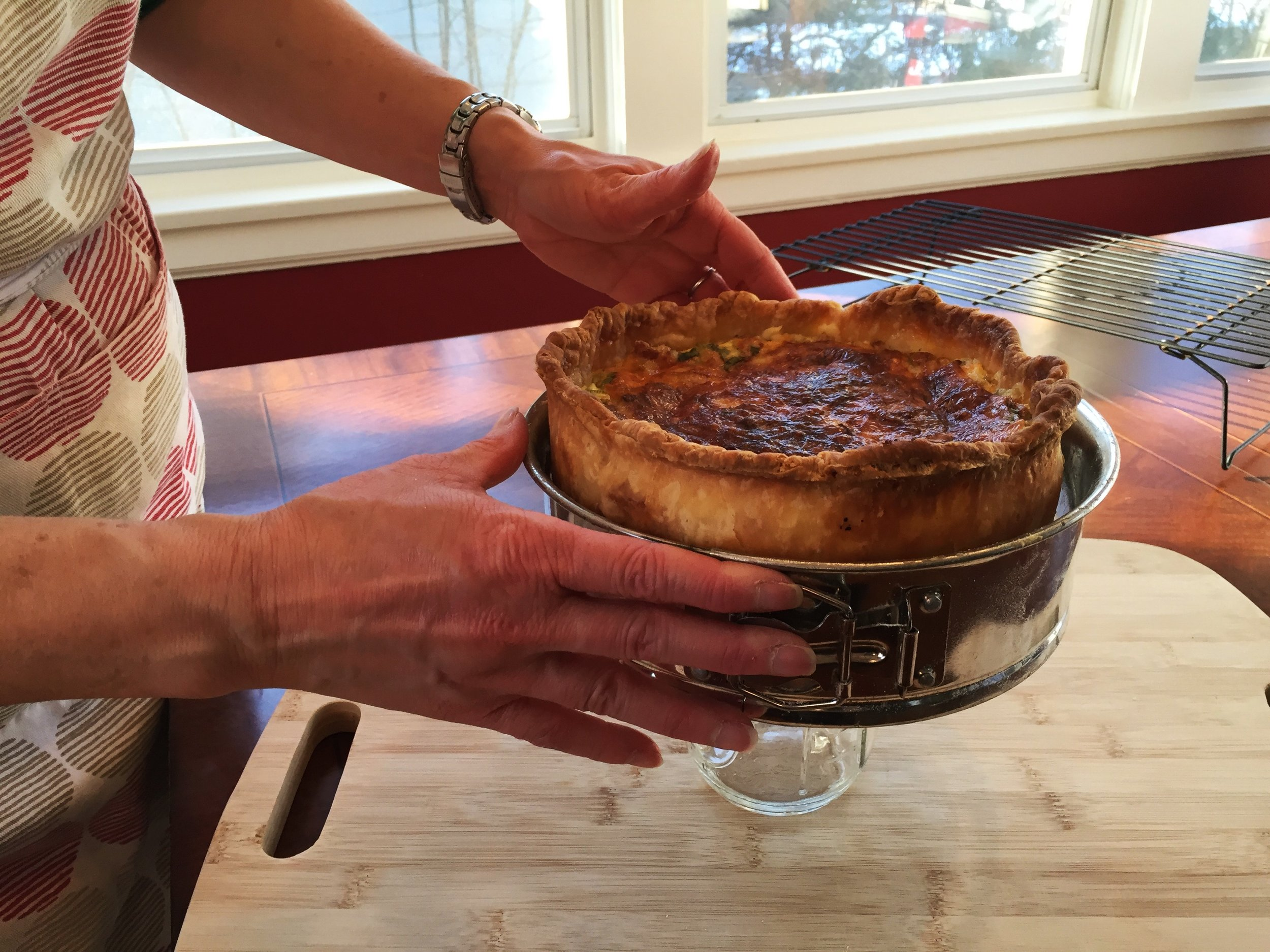 Removing quiche from springform pan. Pan is set on top of a jar, then the outer rim is loosened and slid downward, off of the quiche.