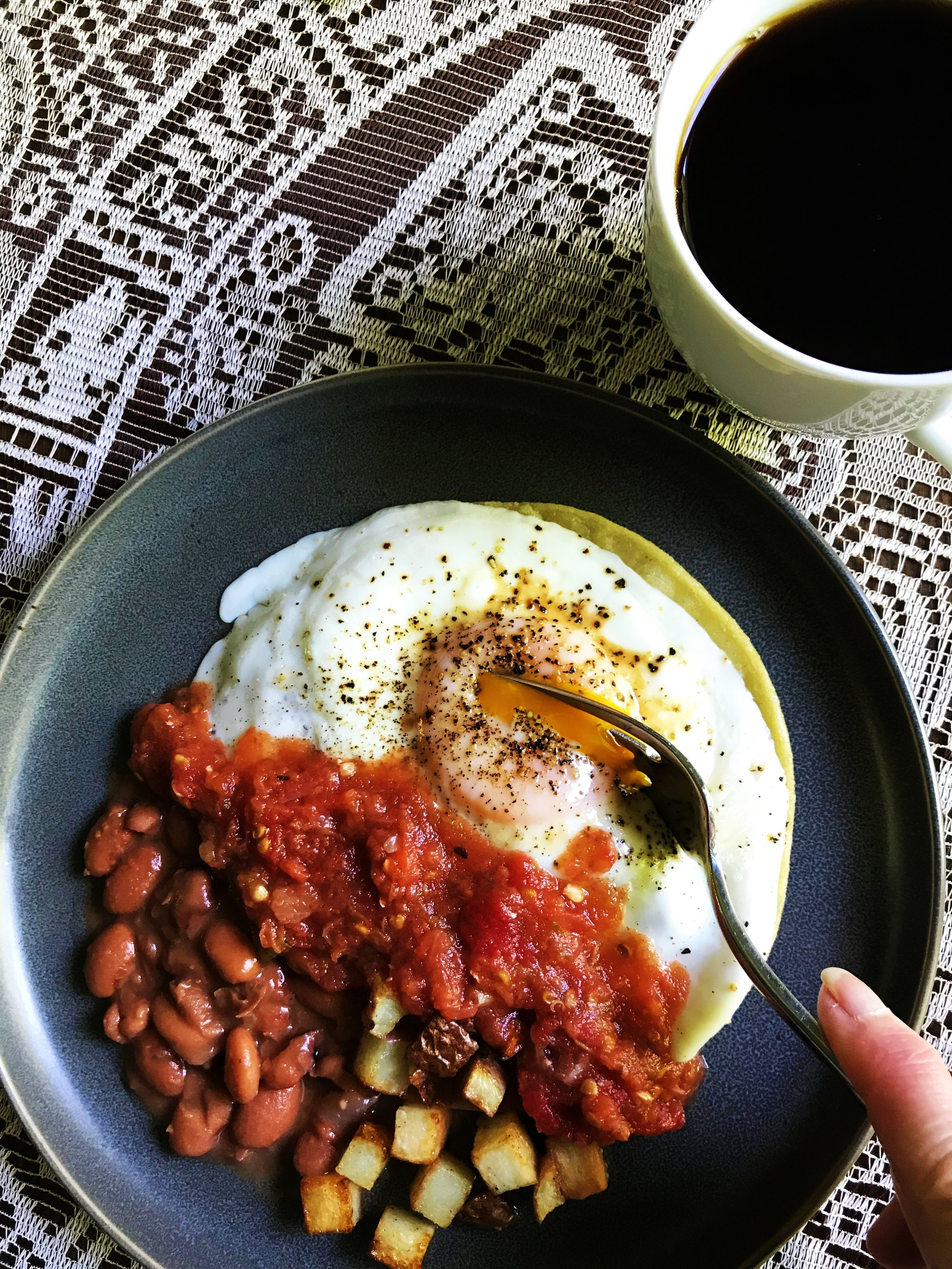 Huevos Rancheros with Salsa de Molcajete and a cup of coffee. I bought the tablecloth in these pictures from a vendor at Teotihuacan, the ancient pyramids outside Mexico City, who told me it was made from maguey plant fibers (an ancient method).