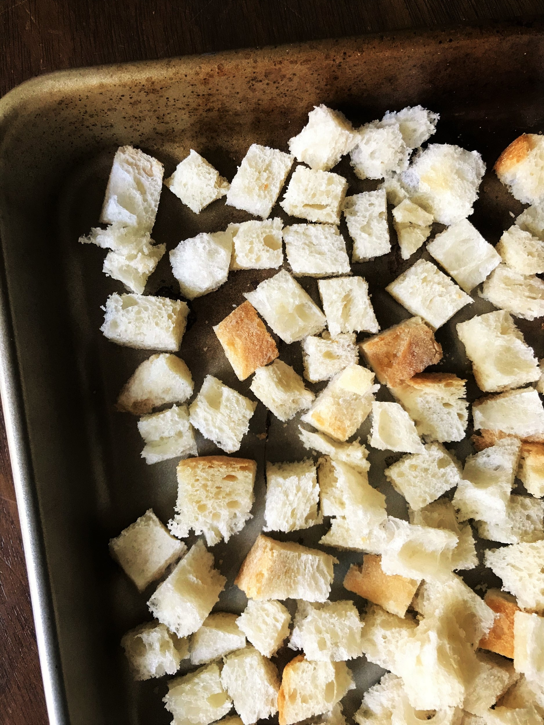 Cubed bread for stuffing, spread out on a baking sheet to dry out.