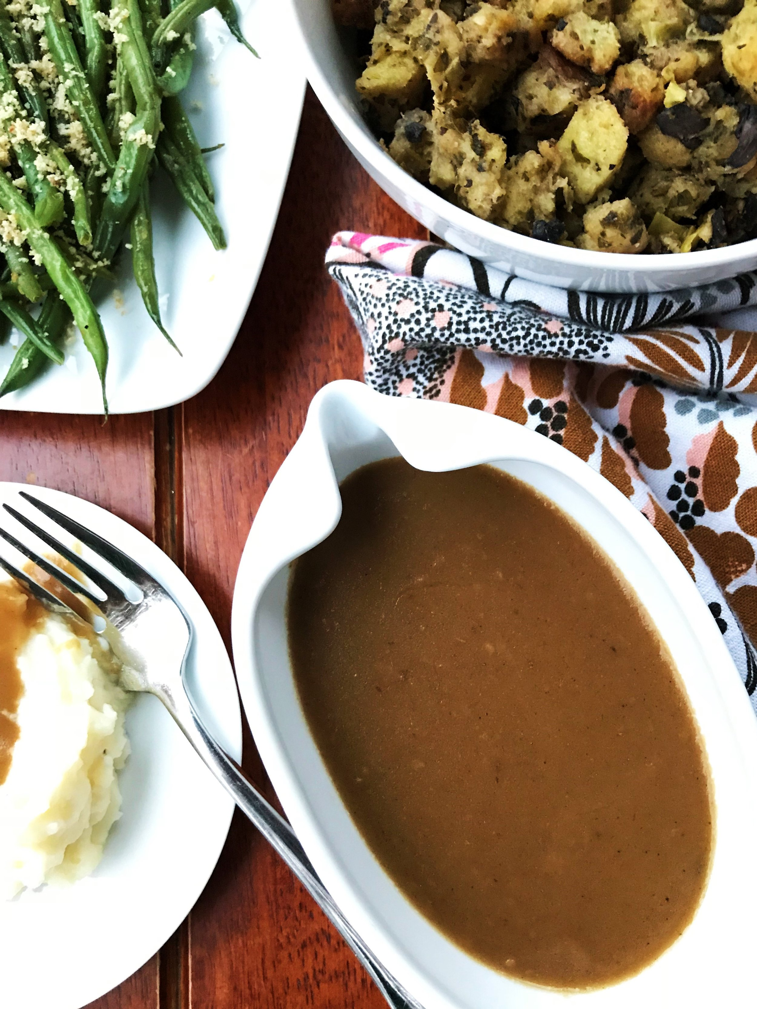 Turkey gravy with mashed potatoes, green beans and stuffing.