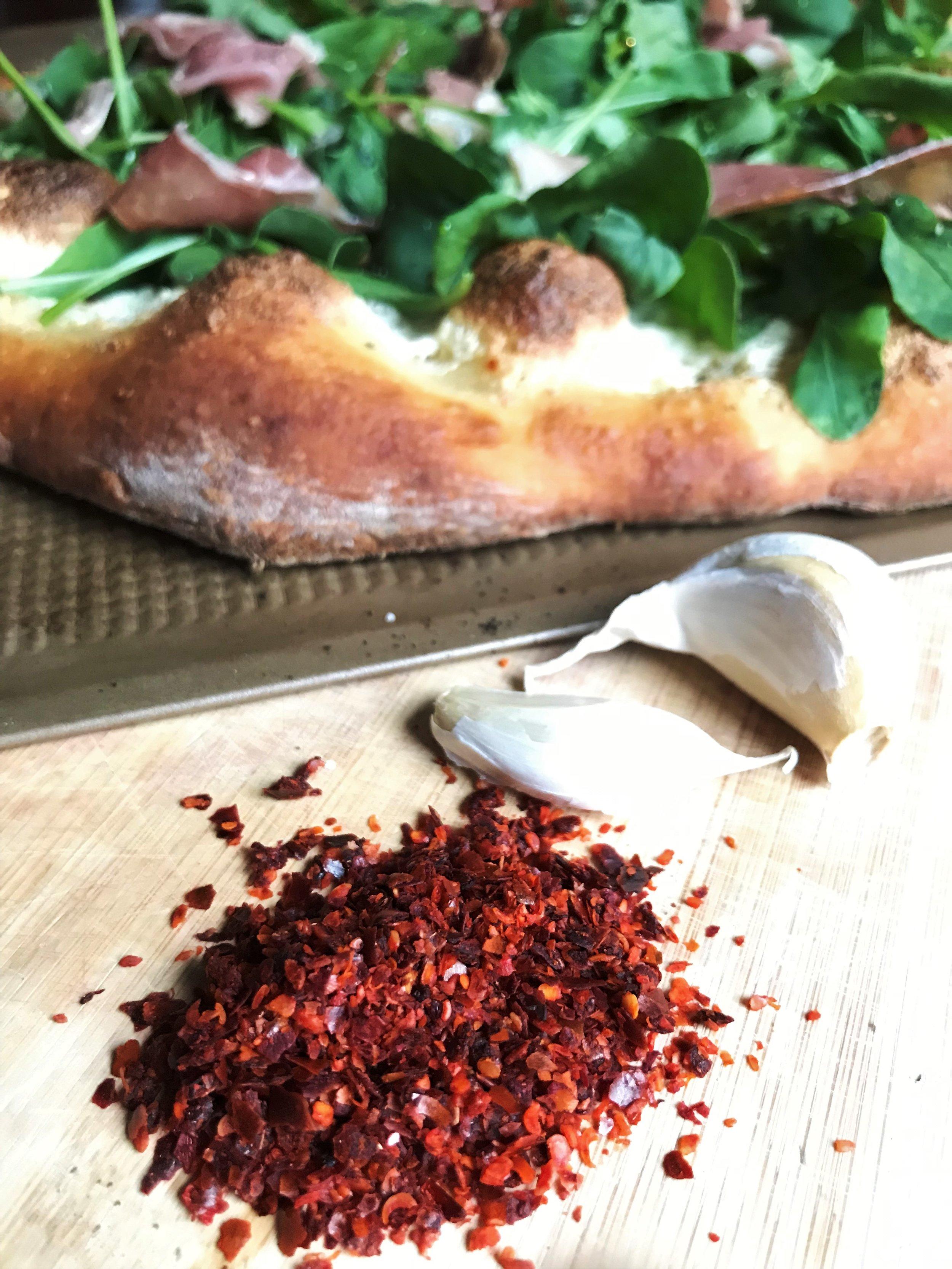 Aleppo pepper with garlic cloves and Arugula and Prosciutto Pizza.jpg